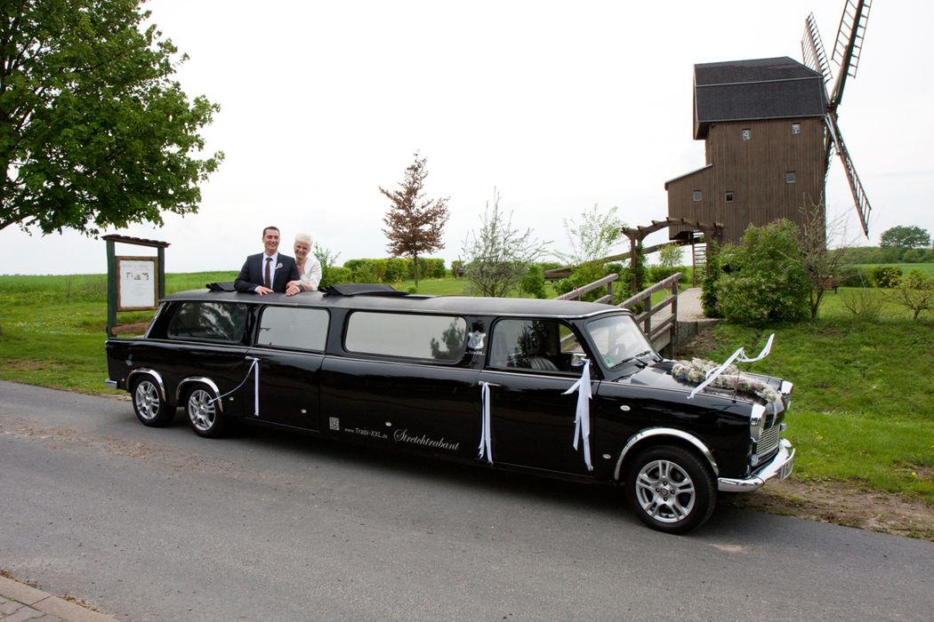 Strahlende Gäste stehend im Auto vor der Hochzeitsmühle