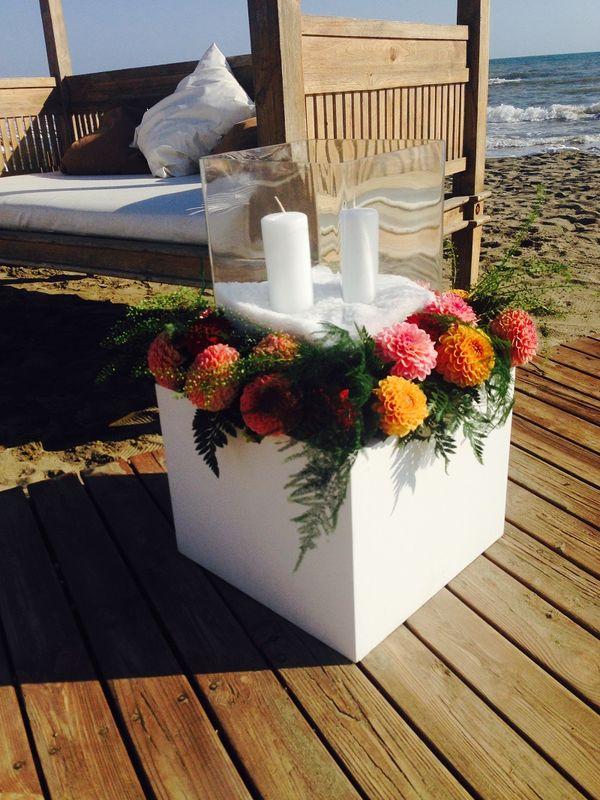 Allestimenti sulla spiaggia con dalie e candele