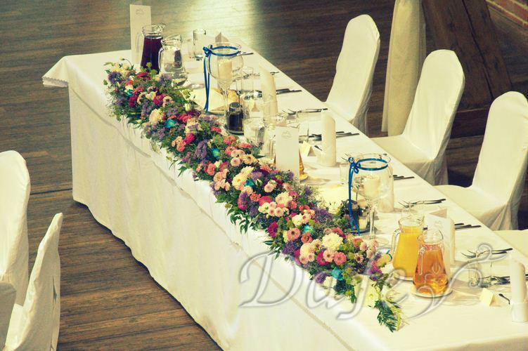 Kompozycje florystyczne zdobiące stół weselny