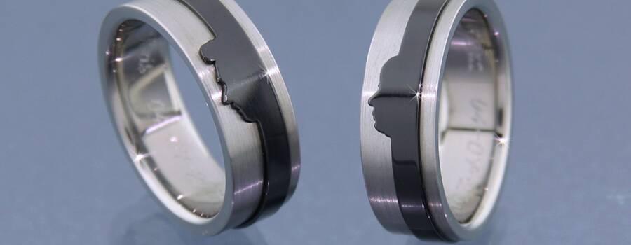 Bijzondere trouwringen, met het gezicht-profiel van je partner. Op de foto in titanium met zwart zirconium, maar natuurlijk ook in goud leverbaar.