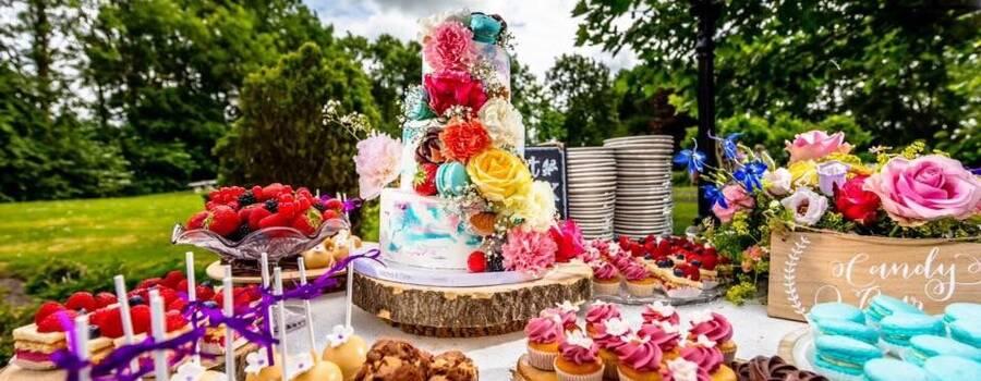 Creme bruidstaart gedecoreerd met echte bloemen en macarons. De tafel is aangevuld met heerlijke zoete hapjes.