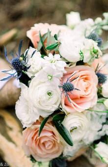 bruidsboeket met zachte kleuren van rozen,  ranonkels en violier aangevuld met een blauwe distel voor het blauwe kleur accent. draadgebonden techniek bij Bruidsboeket & Zo