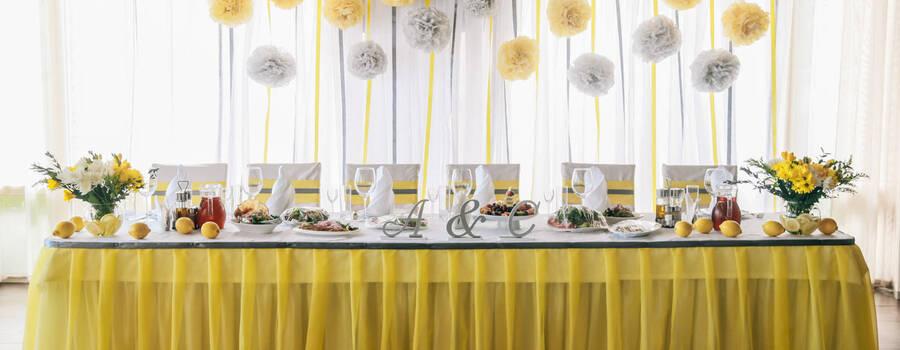 Оформление свадебного президиума тканями, цветами, помпонами, объёмными буквами. Жёлто-серая цветовая гамма.