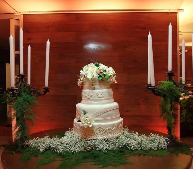 Tradicionalíssimo. Renda em açúcar replicando a do vestido da noiva, finalização com flores de açúcar. Massa bolo de noiva com recheio de creme italiano.