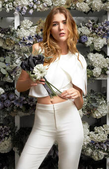 Anita -  This draped top features an exposed waistline and over the shoulder bow. Matching perfectly with the Julia pant, this piece will ensure that you stand out during your wedding weekend. Made in NYC. 100% Polyester. Julia pant sold separately.