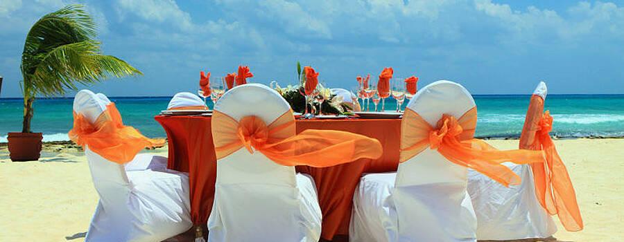 Beispiel: Stuhlhussen mit orangenem Stoff am Strand, Foto: Agentur Traumhaft.