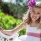 Menina das alianças com vestido branco e faixa rosa.