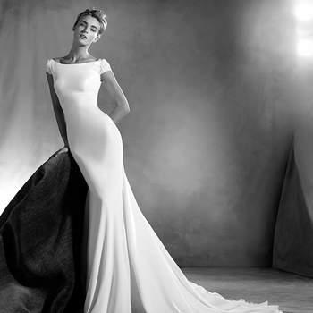 Elegante vestido de noiva em crepe, estilo sereia com decote em barco e requintadas mangas curtas com detalhes de pedraria. Este modelo desenha delicadamente a silhueta da noiva. O pronunciado decote em forma de V das costas, adiciona-lhe um toque sexy.