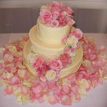 Torta en tres pisos decorada con rosas y rodeada con pétalos del mismo color. Los pétalos desempeñan un papel importante en la decoración.