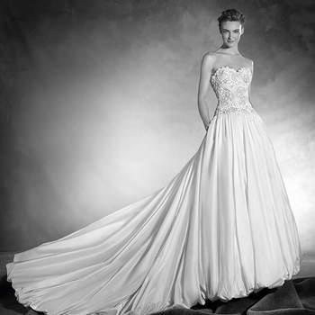 Como uma autêntica princesa de conto de fadas, este vestido de noiva confeccionado em maravilhoso tafetá de seda, corte baixo, decote em coração em tule com aplicações de pedraria e fio bordado, realçam a silhueta de uma noiva deslumbrante.