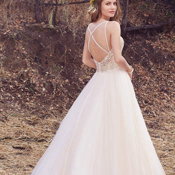 This enchanting ballgown features a bodice accented in beaded embroidery atop a voluminous tulle skirt. Beaded spaghetti straps glide from sweetheart neckline into a scoop back with sheer trim, creating a unique crisscross effect. Finished with crystal buttons over zipper closure. Lined bodice with exposed boning also available