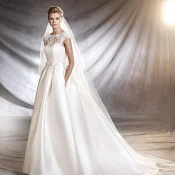 Magnífico vestido de noiva de mikado, corte na cintura, decote em barco e estilo princesa. Uma criação de inspiração clássica com um bonito decote de renda com motivos florais. Um gracioso laço define a figura deste modelo de ares aristocráticos.