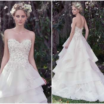 "Romantic and sophisticated, this fitted bodice, adorned with beaded floral appliqués and Swarovski crystal details, falls into a voluminous layered horsehair edged skirt. The soft sweetheart neckline adds an extra dose of femininity to this modern tulle and Chic organza ball gown wedding dress. Finished with covered buttons over zipper and inner corset closure.   <a href=""https://www.maggiesottero.com/maggie-sottero/katherine/9699"" target=""_blank"">Maggie Sottero</a>"