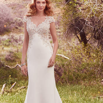 "This glamorous sheath features an elegant Aldora satin skirt and a striking train comprised of illusion lace appliqués. Shimmering pearls accent swirls of beading and embroidered motifs along the gown's V-neckline, cap-sleeves, and illusion low back. Finished with crystal buttons over zipper closure.  <a href=""https://www.maggiesottero.com/maggie-sottero/odette/10128?utm_source=mywedding.com&amp;utm_campaign=spring17&amp;utm_medium=gallery"" target=""_blank"">Maggie Sottero</a>"