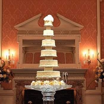 Torta de 6 pisos colocada sobre una base muy amplia rodeada de muchas rosas, ideal para una boda elegante.