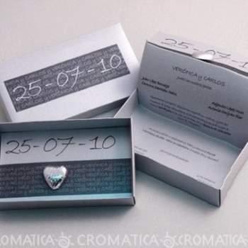 Caja rectangular en color plateado con fecha de la boda en la portada, al interior hoja con la invitación más un corazón plateado.