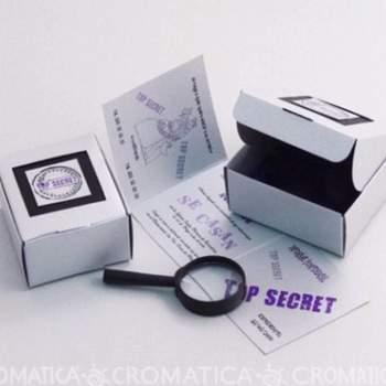 """Caja misteriosa en color blanco cuadrada con sello """"top secret"""" adentro encuentra un plegable con la invitación a la boda, una lupa."""