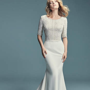 "<a href=""https://www.maggiesottero.com/maggie-sottero/edalene/11468"">Maggie Sottero</a>  This modest sleeved wedding dress features an allover lace bodice with elegant elbow-length sleeves and a scoop neckline. Soft sheath skirt is comprised of Aldora Crepe. Finished with zipper closure."