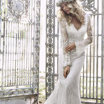 "Perfect for either the garden or church wedding, this romantic, lace sheath gown speaks to the free-spirited bride inspired by nature. Featuring long sleeves, and accented with three dimensional floral embellishments and Swarovski crystals. Finished with zipper back closure.   <a href=""http://www.maggiesottero.com/dress.aspx?style=5HS158"" target=""_blank"">Maggie Sottero Spring 2015</a>"