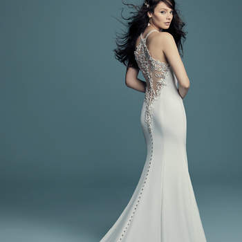 "<a href=""https://www.maggiesottero.com/maggie-sottero/maurelle/11496"">Maggie Sottero</a>  Swarovski crystals and beaded lace motifs cascade along the illusion plunging keyhole neckline and illusion halter back in this sexy wedding dress, comprised of Aldora crepe. Crystal buttons drift from zipper to hemline."