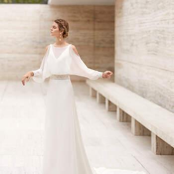 O encantador vestido Elkan apresenta uma combinação de tecidos que são uma explosão de elegância. Com silhueta em A, uma essência divina e uma manga comprida vaporosa, é ideal para um casamento na praia ou uma cerimónia eclesiástica de primavera ou outono.