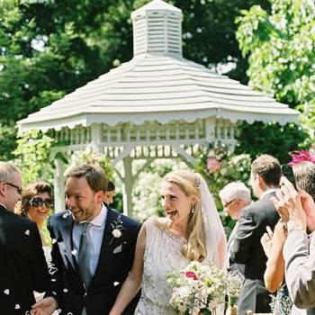 Los novios recién casados saliendo de la ceremonia por el pasillo central.