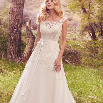 "Embroidered lace appliqués cascade over the bodice, illusion sweetheart neckline, and illusion cap-sleeves of this gorgeous A-line, featuring a keyhole back and tulle skirt. Finished with covered buttons over zipper closure. Style includes grosgrain ribbon belt.  <a href=""https://www.maggiesottero.com/maggie-sottero/ophelia/10129?utm_source=mywedding.com&amp;utm_campaign=spring17&amp;utm_medium=gallery"" target=""_blank"">Maggie Sottero</a>"