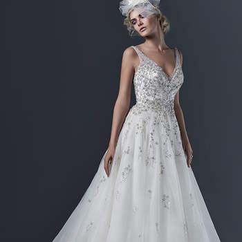 """Vestido de novia etéreo con líneas simples de corte A. El modelo cuenta con tirantes y escote uve, así como aplicaciones de cristales en todo el cuerpo. La falda es amplia y termina en cauda,. El cierre de este modelo es con cremallera.    <a href=""""http://www.sotteroandmidgley.com/dress.aspx?style=5SR600"""" target=""""_blank"""">Sottero &amp; Midgley</a>"""