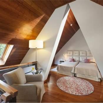 """Mezcla de ambientes cálidos y modernos en una misma habitación, con un espacio muy diferenciado en la zona de la cama y la parte de la suite correspondiente al descanso o el ocio, es la propuesta de las habitaciones del Parador de Artíes. Foto: <a href=""""http://zankyou.9nl.de/wdbk"""" target=""""_blank"""">Paradores</a><img src=""""http://ad.doubleclick.net/ad/N4022.1765593.ZANKYOU.COM/B7764770.4;sz=1x1"""" alt="""""""" width=""""1"""" border=""""0"""" /><img height='0' width='0' alt='' src='http://9nl.de/xyl3' />"""