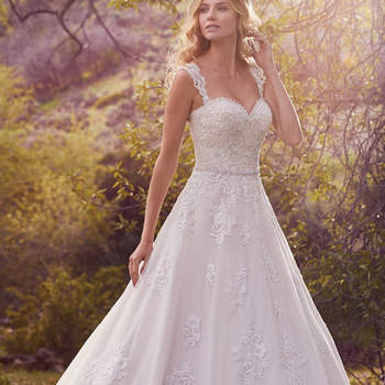 "This breathtaking A-line features lace appliqués, shimmering embroidery, and a scalloped hem accented with exquisite pearls and beading. Finished with covered  buttons over zipper and inner corset closure. Detachable cap-sleeves with lace appliqués sold separately.   <a href=""https://www.maggiesottero.com/maggie-sottero/reba/10134?utm_source=mywedding.com&amp;utm_campaign=spring17&amp;utm_medium=gallery"" target=""_blank"">Maggie Sottero</a>"