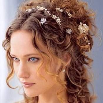 Cabello largo desordenado con risos peinado a la mitad adornado con flores pequeñas.
