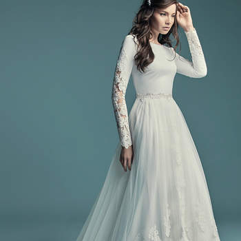 "<a href=""https://www.maggiesottero.com/maggie-sottero/olyssia/11500"">Maggie Sottero</a>  This elegant sleeved wedding dress is comprised of Talin Stretch Crepe. Featuring a bateau neckline, scoop back, and lace illusion along the long sleeves. Finished with covered and crystal buttons over zipper closure. Detachable overskirt accented in lace sold separately."