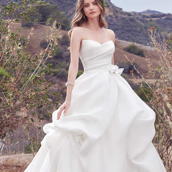 This simple yet glamorous Cameo Organza ballgown features a softly pleated bodice and voluminous pickups in the skirt. A distinctive sweetheart neckline and handmade 3D floral motif, accented with Swarovski crystals, at the hip and skirt add unique romance to this look. Finished with zipper closure.
