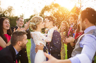 Wedding couple kissing surrounded by guests.