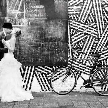"""«É uma foto irreverente com um estilo urbano. Desafia o estilo """"glamour"""", comum em fotografia de casamento. Gosto particularmente da atitude descontraída dos noivos e das texturas contrastantes no background, onde se pode ler """"Hard to find, Easy to Love"""". Revela o lado alternativo de Amesterdão em contraste com um elemento classico, a icónica bicicleta.»  www.sweetlemonade.nl"""