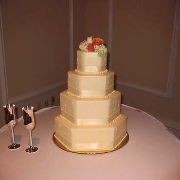 Deseas una torta sencilla y a la vez elegante, en cuatro pisos decorada con cinta del mismo tono de la cubierta y un discreto adorno con flores en la parte superior.