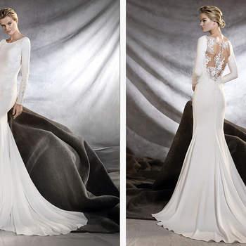 Elegante vestido de novia con escote barco y manga larga de estilo sirena que realza la silueta femenina. Una propuesta de crepe, chantilly, guipur y tul con motivos florales.