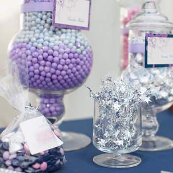 Mesa de dulces en colores violetas, azules y plateados lucen tentadores para tus invitados.