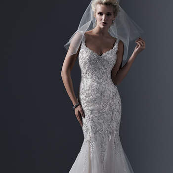 Lace appliqués, decadently embroidered with dramatic sequins and Swarovski crystals, adorn the bodice of this tulle fit and flare wedding dress, with daring scoop back and romantic sweetheart neckline. Finished with crystal buttons over zipper closure. <img height='0' width='0' alt='' src='http://ads.zankyou.com/mn8v' />