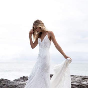 Vestido de novia de tirantes y de encaje en color blanco roto.