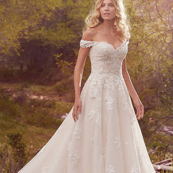 "This timeless yet alluring ballgown features off-the-shoulder sleeves, a V-back, and a sweetheart neckline. Shimmering beads accent delicate cascades of lace along the gown's bodice and tulle skirt. Finished with covered buttons over zipper and inner corset closure.  <a href=""https://www.maggiesottero.com/maggie-sottero/saffron/10140?utm_source=mywedding.com&amp;utm_campaign=spring17&amp;utm_medium=gallery"" target=""_blank"">Maggie Sottero</a>"