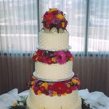 Torta en cuatro pisos donde la decoración es con plantas verdes y flores rojas.
