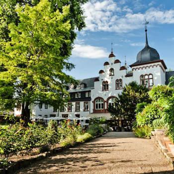 Hotel Kronenschlösschen: Das luxuriöse Kronenschlösschen ist das Hochzeits-Hotel par excellence. Im romantischen Dörfchen Hattenheim, – mit seinen Fachwerkhäusern, alten Straßen und Gassen, mit der historischen Burg und der Barockkirche St. Vincent einer der schönsten Orte im Rheingau – liegt das Hotel Kronenschlösschen inmitten eines Privatparks mit Blick auf den Rhein.