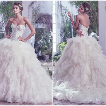 "Airy tulle and Chic organza create the dreamy and alluring skirt of this grand ball gown wedding dress, artistically embellished with beading and Swarovski crystals, fitted bodice and romantic sweetheart neckline. Finished with covered buttons over zipper and inner corset closure. Available with extended train (16"" longer), Castalia Marie.  <a href=""https://www.maggiesottero.com/maggie-sottero/castalia/9688"" target=""_blank"">Maggie Sottero</a>"