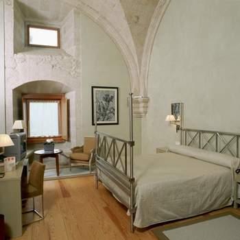 """Contar con arcadas y bóvedas dentro de tu habitación en la noche de bodas es algo que solo podrás obtener en edificios históricos como los que acogen los Paradores. Esta habitación del Parador del Santo Estevo es un ejemplo de ello. Foto: <a href=""""http://zankyou.9nl.de/wdbk"""" target=""""_blank"""">Paradores</a><img src=""""http://ad.doubleclick.net/ad/N4022.1765593.ZANKYOU.COM/B7764770.4;sz=1x1"""" alt="""""""" width=""""1"""" border=""""0"""" /><img height='0' width='0' alt='' src='http://9nl.de/xyl3' />"""