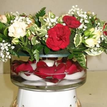 Pauline. Oeillets rouges, roses champagnes, gypsophile et verdure, cette composition est travaillée sur verre avec bougies flottantes et pétales de roses - Crédit photo: Twenga