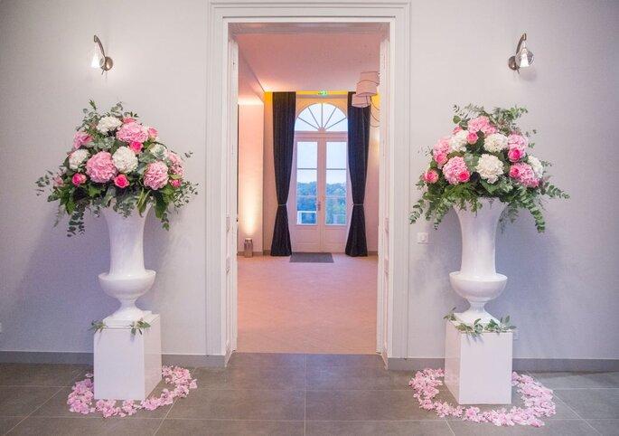 Le Domaine des Cormellas, deux grands vases fleuris avec des fleurs roses et blanche à l'entrée de la salle de réception