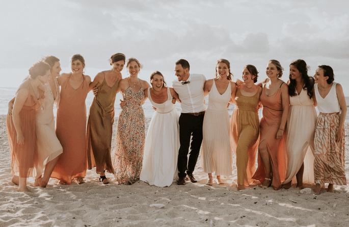 Des invités entourant un couple de mariés sur une plage