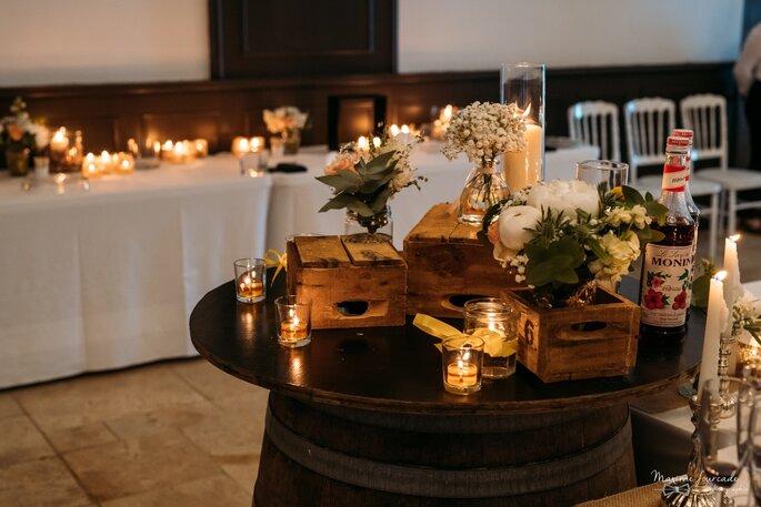 Décoration de table pour un mariage composée de bouquets de fleurs, de bougies, et de caisses en bois pour une ambiance tamisée bohème