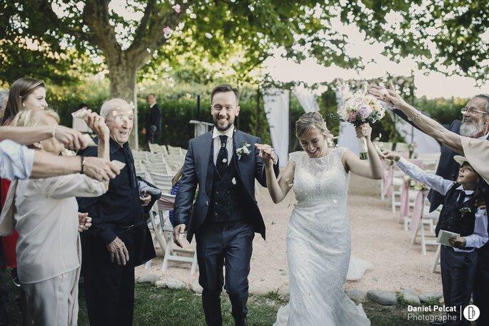 Lancé de riz suite à une cérémonie laïque, haie d'honneur d'invités que les mariés saluent en passant et en souriant